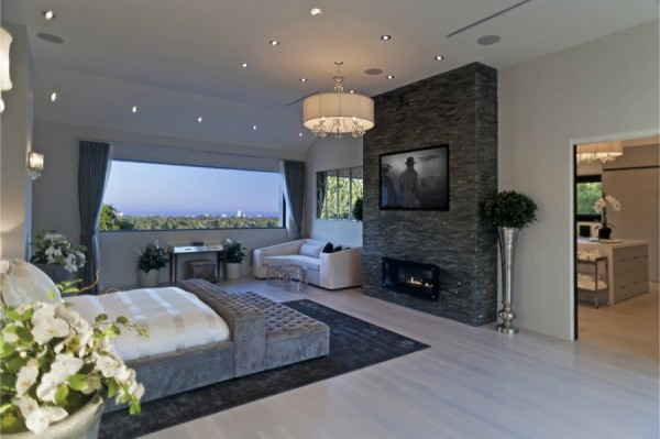 the-master-bedroom-has-a-huge-fireplace-with-the-tv-above-it.jpg