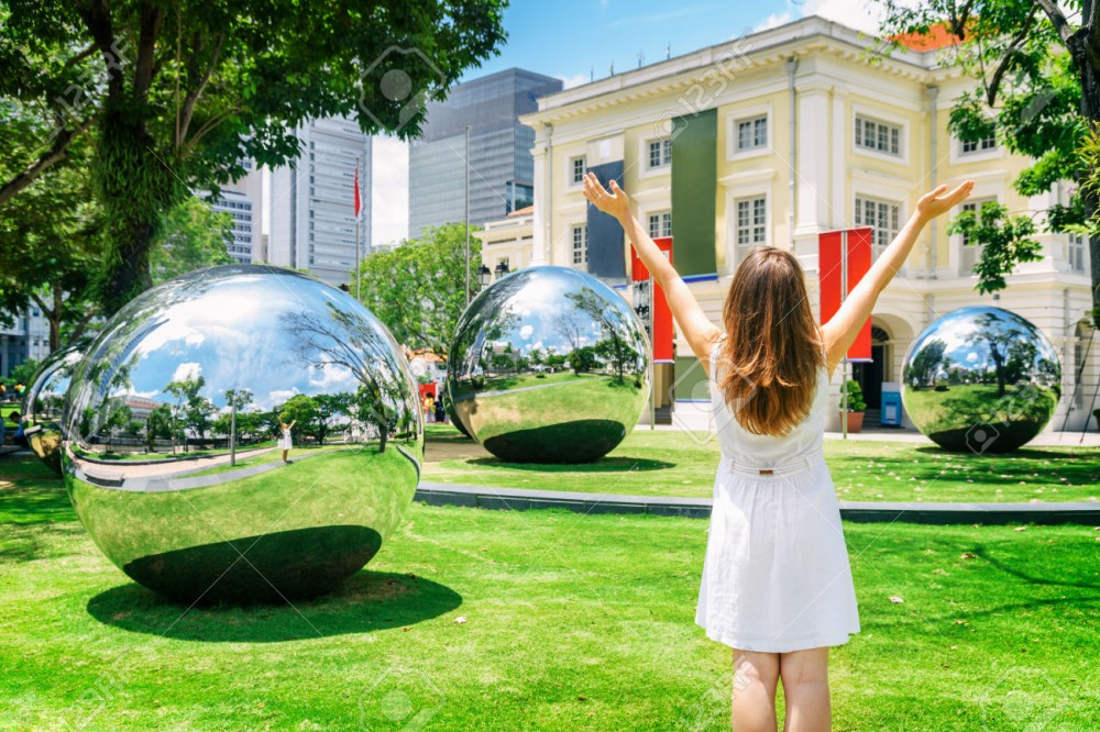 78463788-Girl-with-raised-arms-to-the-sky-among-amazing-large-mirror-balls--Stock-Photo.jpg